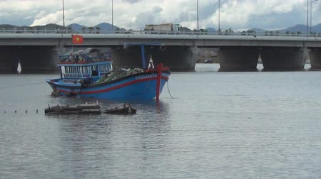 var : Vietnamese blue boat at anchor on the river. fishermen throwing fishing nets into the boat. in the background there is a bridge Stok Video