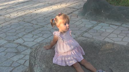 preguiça : beautiful baby sitting on a large rock. She is wearing a dress. She looks at the sky and on the sides. baby saw something, she is surprised and points to the side.