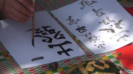 японский рисунок : An man is practicing calligraphy using a brush pen in his leisure time