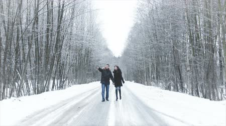 congelado : Girl and boy walking along the road into the woods. hold hands. they kiss