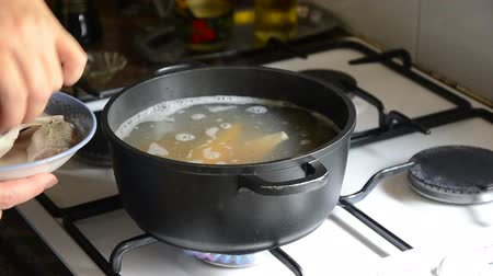 cooking pots : Cooking fish pieces in a black pot