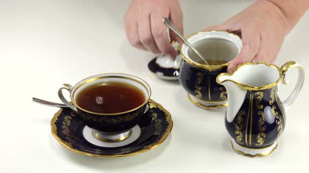 ложка : Adding brown sugar to cup of tea