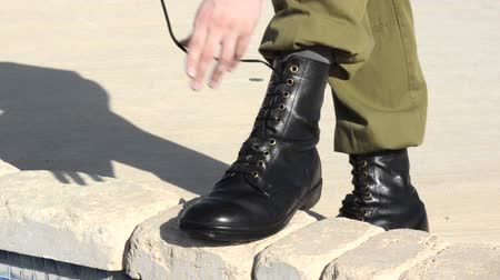uniforme : Soldier tying his military boots