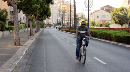 kippur : Rishon LeZion, Israel - October 4,2014: Unidentified black man baking on deserted city road. Once a year, on Yom Kippur (Jewish Day of Atonement) the country goes quiet as almost all cars stop running