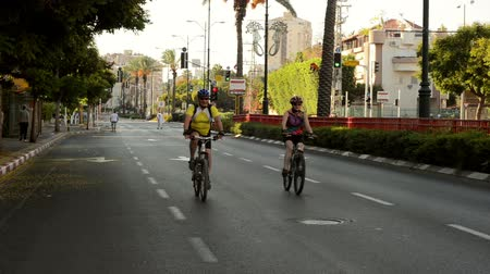 kippur : Rishon LeZion, Israel - October 4,2014: Unidentified family couple biking on car-less city road. Once a year, on Yom Kippur (Jewish Day of Atonement) the country goes quiet as almost all cars stop running