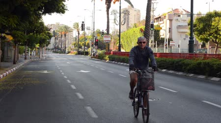 kippur : Rishon LeZion, Israel - October 4,2014: Unidentified aged man bikes in car-less city. Once a year, on Yom Kippur (Jewish Day of Atonement) the country goes quiet as almost all cars stop running