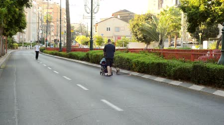 kippur : Rishon LeZion, Israel - October 4,2014: Unidentified man rolls the stroller on the car-less road. Once a year, on Yom Kippur (Jewish Day of Atonement) the country goes quiet as almost all cars stop running