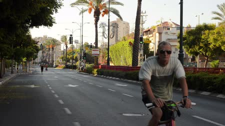 kippur : Rishon LeZion, Israel - October 4,2014: Unidentified gray-haired man rides bicycle on deserted city road. Once a year, on Yom Kippur (Jewish Day of Atonement) the country goes quiet as almost all cars stop running