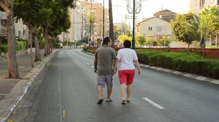 kippur : Rishon LeZion, Israel - October 4,2014: Unidentified middle-aged couple walking along the deserted road. View from the back. Once a year, on Yom Kippur (Jewish Day of Atonement) the country goes quiet as almost all cars stop running Stock Footage