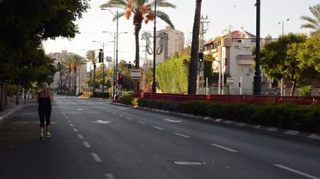 kippur : Rishon LeZion, Israel - October 4,2014: Unidentified mature woman running on empty road. Once a year, on Yom Kippur (Jewish Day of Atonement) the country goes quiet as almost all cars stop running Stock Footage