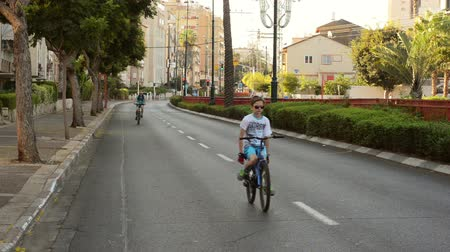 kippur : Rishon LeZion, Israel - October 4,2014: Unidentified son and father bike in deserted city. Once a year, on Yom Kippur (Jewish Day of Atonement) the country goes quiet as almost all cars stop running