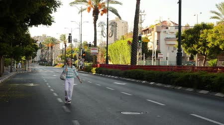 kippur : Rishon LeZion, Israel - October 4,2014: Unidentified woman walking and talking by cell phone on deserted city road. Once a year, on Yom Kippur (Jewish Day of Atonement) the country goes quiet as almost all cars stop running Stock Footage