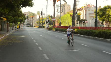 kippur : Rishon LeZion, Israel - October 4,2014: Unidentified kid riding on a bicycle very fast on deserted city road. Once a year, on Yom Kippur (Jewish Day of Atonement) the country goes quiet as almost all cars stop running.