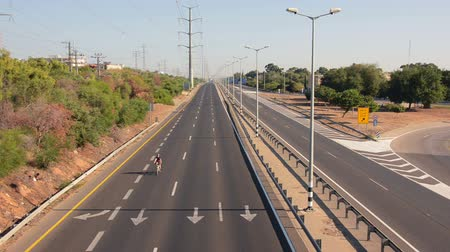kippur : Two cyclists go one by one on car-less motorway. Once a year, on Yom Kippur (Jewish Day of Atonement) the country goes quiet as almost all cars stop running