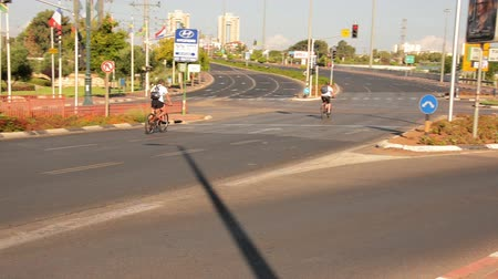 kippur : Rishon LeZion, Israel - October 4,2014: Two unidentified men bike on deserted city road. Once a year, on Yom Kippur (Jewish Day of Atonement) the country goes quiet as almost all cars stop running. Stock Footage