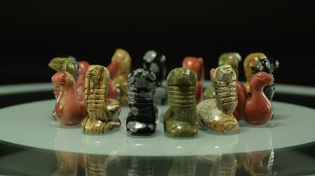 semi precious : Assorted stone snakes statuettes rotate on black background