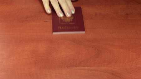 pas : False Russian passport obtaining vs thick white envelope. Hands movement on the wooden surface table