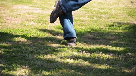 embarrassed : Man in blue jeans cleans his footwear poop off on lawn grass