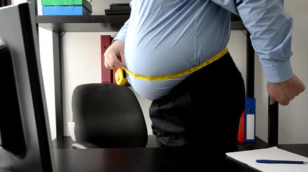 tłuszcz : Businessman measures his big waist after lunchtime Wideo