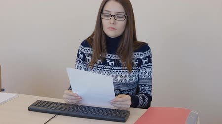 office worker is typing, office girl looking at a document and print to your computer Stock Footage