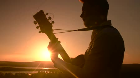 akustik : Young attractive caucasian man sitting outdoors and playing guitar at sunset Stok Video