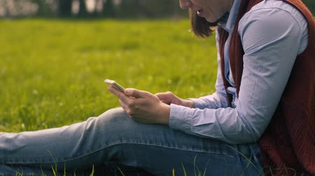 ismeretlen : Woman Typing Text On A Smartphone Sitting On Lawn
