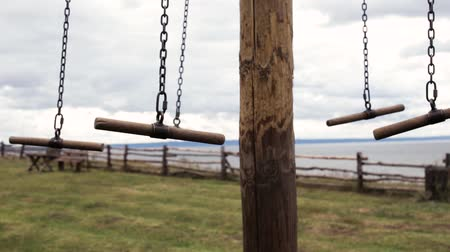 Empty Swing On Chain Swing Against Of Gray Clouds