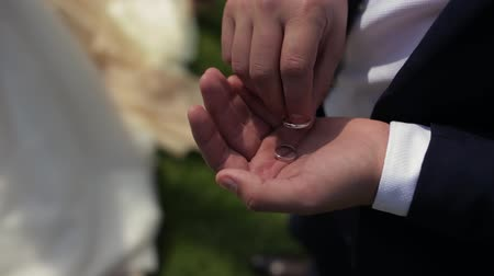 Bride And Groom Hold Wedding Rings During Wedding