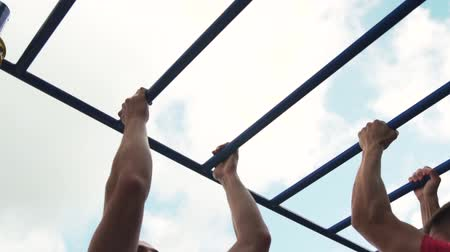 horizontal bar : Two Muscular Male Adults Practicing Street Workout Exercises