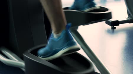 stanovena : Male Legs During Workout on Elliptical Machine