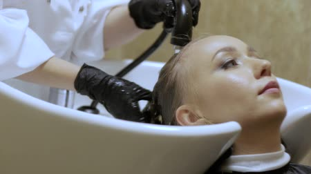 faíscas : Professional Hairdresser Washing Female Hairs Before Haircut in a Beauty Salon Stock Footage
