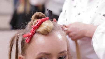 emaranhado : Professional Hairdresser making a hairdo to a fair-haired model