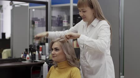 corrugated : Positive Woman Hairdresser Make A Voluminous Beautiful Hairstyle Stock Footage