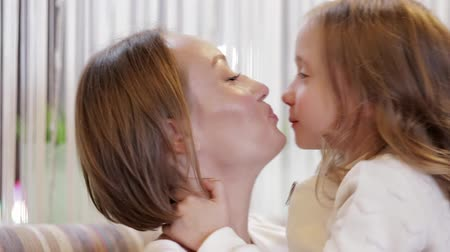csókolózás : Mother And Charming Daughter Hugging And Kissing While Sitting In A Cozy Home
