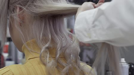 oluklu : The Hairdresser Makes Beautiful, Elegant Curls Of A Client Girl With Blond Hair