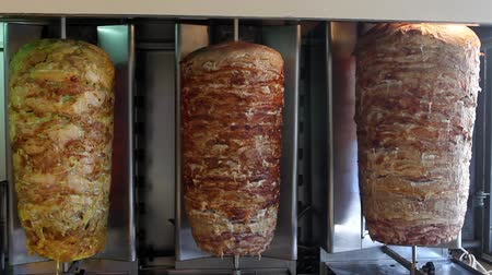 kebap : A pair of rotating skewered chicken and lamb meat grilled and ready to serve in a typical Middle Eastern sandwich Stok Video