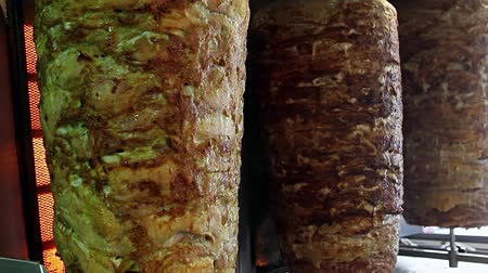 makedonia : A pair of rotating skewered chicken and lamb meat grilled and ready to serve in a typical Middle Eastern sandwich Stock Footage
