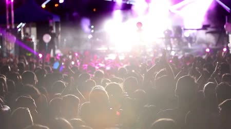 Defocus silhouettes of concert crowd in front of bright stage lights