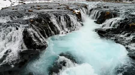 panoramic view : Aerial flight with drone over the famous Bruarfoss waterfall with turquoise water and snow in winter, South Iceland