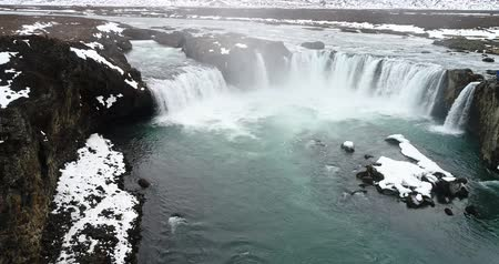 Aerial flight with drone over the famous Godafoss  waterfall with turquoise water and snow in winter, Iceland. Stock Footage