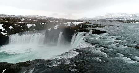 Aerial flight with drone over the famous Godafoss  waterfall with turquoise water and snow in winter, Iceland. Stok Video