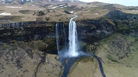 Aerial flight with drone over the famous Seljalandsfoss waterfall , Iceland. Slow motion shot
