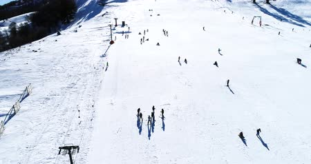 yamaç : Vasilitsa, Greece - January 5, 2018: Aerial View of skiers at Ski Resort Vasilitsa in the mountain range of Pindos, in Greece. The ski resorts currently has 5 lifts and 16 ski trails Stok Video