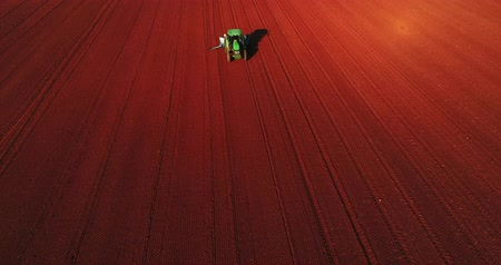 Kilkis, Greece - April 28, 2018: Aerial shot of  Farmer with a tractor on the agricultural field sowing. tractors working on the agricultural field in spring. Cotton seed