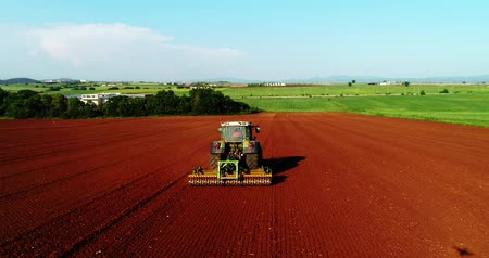 ploughing : Kilkis, Greece - April 28, 2018: Aerial shot of  Farmer with a tractor on the agricultural field sowing. tractors working on the agricultural field in spring. Cotton seed