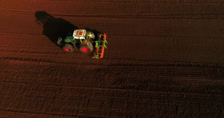 tırmık : Kilkis, Greece - April 28, 2018: Aerial shot of  Farmer with a tractor on the agricultural field sowing. tractors working on the agricultural field in spring. Cotton seed