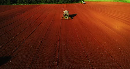 agronomia : Kilkis, Greece - April 28, 2018: Aerial shot of  Farmer with a tractor on the agricultural field sowing. tractors working on the agricultural field in spring. Cotton seed