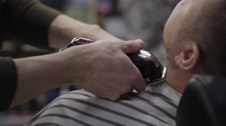 barber trimming beard to his client