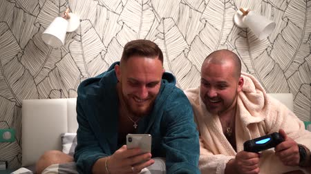 çok güzel : Two bearded men on bed in bathrobe look in phone and very surprised. Slow motion