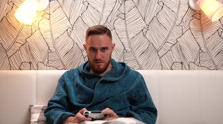 çok güzel : Bearded man in green bathrobe play video game, win and very happy about it.